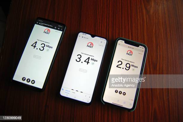 Cellphone dealer runs internet connection speed test on cellphones in Srinagar on February 06, 2021 as Indian government restored high speed 4G...