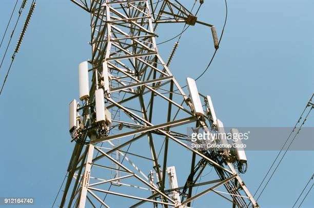 Cellular telephone transmission tower antennas and other hardware are installed on the side of a high tension electrical pylon in the Silicon Valley...