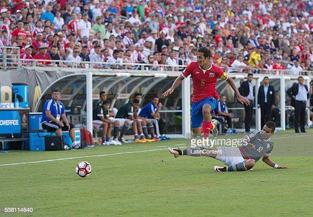 Celso Borges of Costa Rica is tackled by Derlis Gonzalez of Paraguay at the group A match between Costa Rica and Paraguay at Camping World Stadium as...