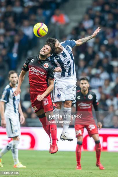 Celso Ortiz of Monterrey heads the ball with Jose Rivero of Tijuana during the third round match between Monterrey and Tijuana as part of Torneo...