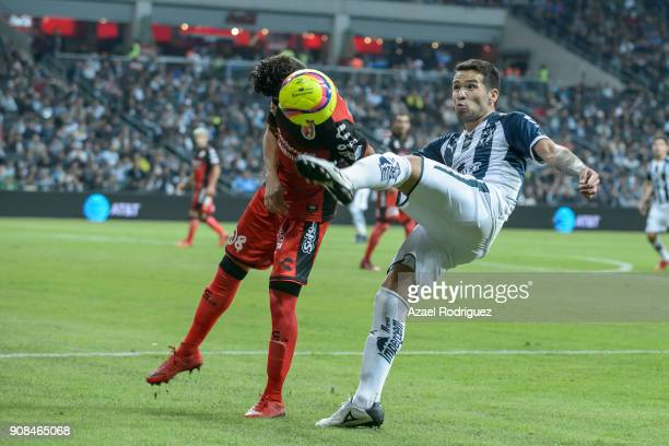 Celso Ortiz of Monterrey kicks the ball over Jose Rivero of Tijuana during the third round match between Monterrey and Tijuana as part of Torneo...