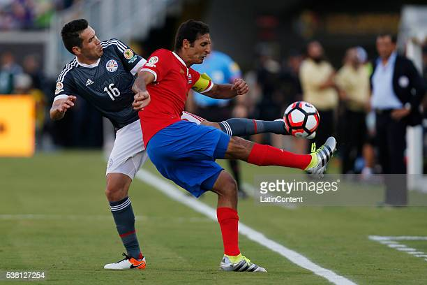 Celso Ortiz of Paraguay battles for the ball against Cristian Gamboa of Costa Rica during a group A match between Costa Rica and Paraguay at Camping...
