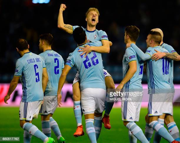 Celta Vigo's Danish midfielder Daniel Wass celebrates with teammates after scoring during the UEFA Europa League round of 16 first leg football match...