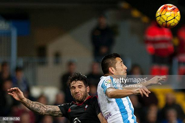 Celta Vigo's defender Carles Planas vies with Malaga's Brazilian forward Charles Dias de Oliveira during the Spanish league football match Malaga CF...