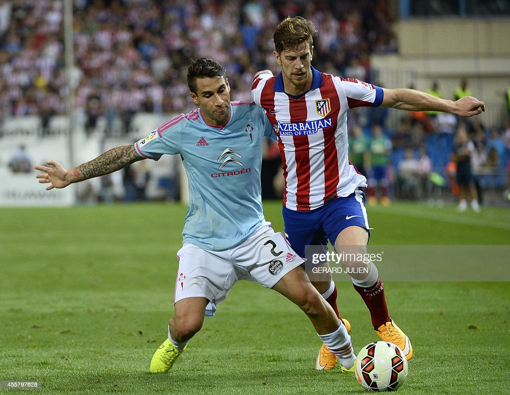 Celta Vigo's defender Hugo Mallo (L) vies with Atletico Madrid's Argentinian defender Cristian Ansaldi during the Spanish league football match Club Atletico de Madrid vs Celta de Vigo at the Vicente Calderon stadium in Madrid on September 20, 2014. The game ended in a draw 2-2.