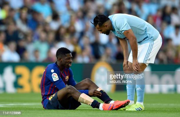Celta Vigo's Moroccan midfielder Sofiane Boufal checks on Barcelona's French forward Ousmane Dembele after resulting injured during the Spanish...