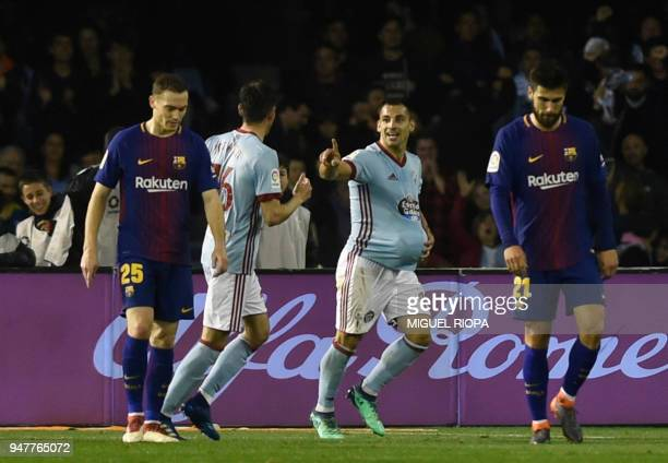 Celta Vigo's Spanish defender Jonny Castro celebrates a goal between Barcelona's Belgian defender Thomas Vermaelen and Portuguese midfielder Andre...