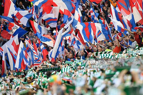Celtic and Rangers wave flags during the Ladbrokes Scottish Premier league match between Celtic and Rangers at Celtic Park Stadium on September 10...