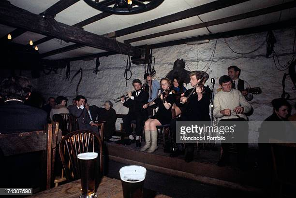 A Celtic band is playing live music in a pub in Dublin on the platform in the front line from left a transverse flute two violins and a spoon in the...