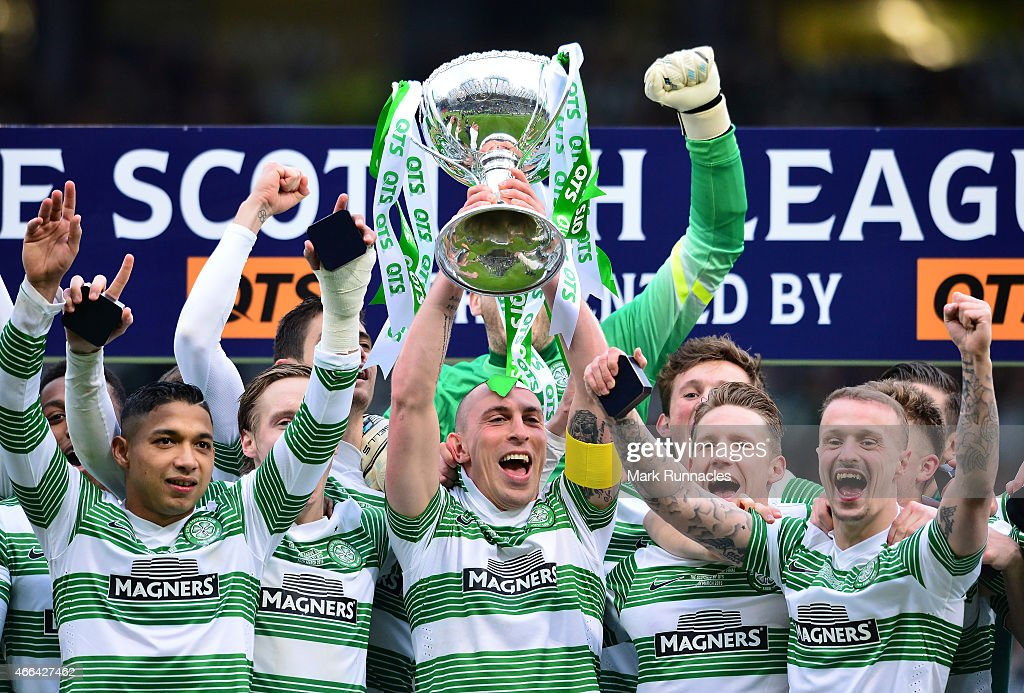 Celtic captain Scott Brown is presented with the League Cup trophy by life long Celtic fan Rod Stewart (L), as the Celtic team celebrate during the Scottish League Cup Final between Dundee United and Celtic at Hamden Park on March 15, 2015 in Glasgow Scotland.