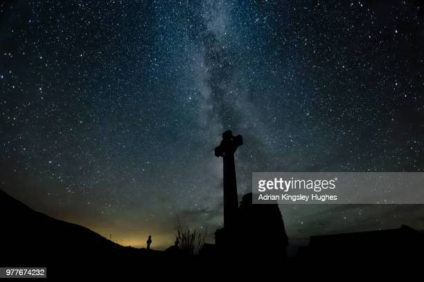 Celtic cross against night sky full of stars, Bardsey Island, Wales, UK