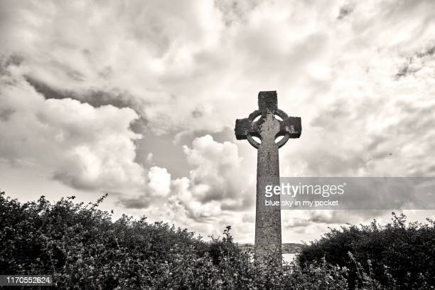 a celtic cross on the island of iona, scotland - celtic knot stock photos and pictures
