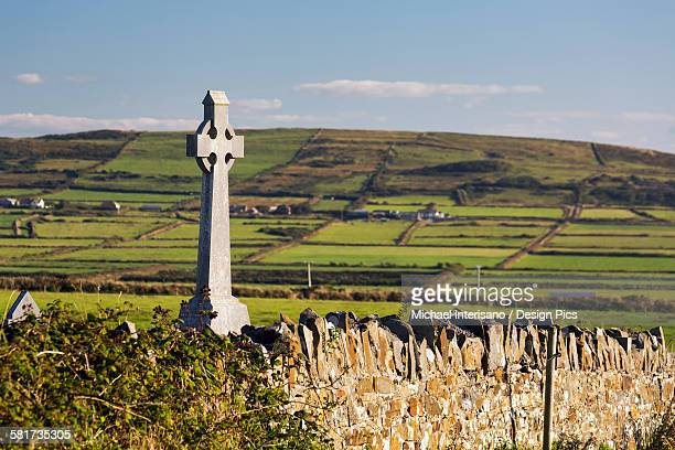 Celtic cross with stone fence and hilly grass fields in the distance with blue sky