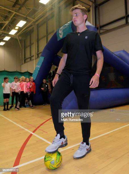 Celtic fan Aidan McHugh of Great Britain messing around with a football during a tennis activity session with local children on the fourth day of The...
