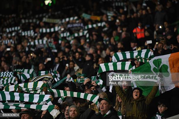 Celtic fans hold up team scarves in the stands during the UEFA Champions League group stage football match between Celtic and Barcelona at Celtic...