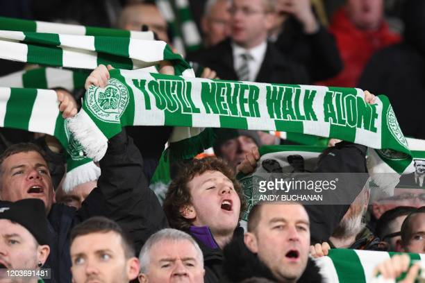 Celtic fans raise their scarves as they sing in the crowd before kick off in the UEFA Europa League round of 32 second leg football match between...