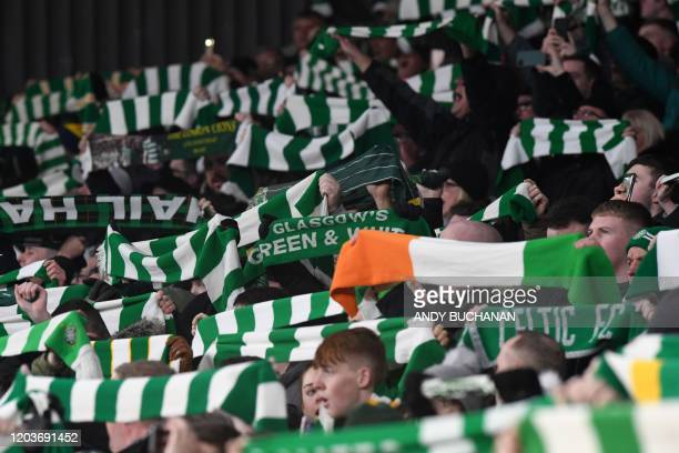 Celtic fans raise their scarves in the crowd before kick off in the UEFA Europa League round of 32 second leg football match between Celtic and...