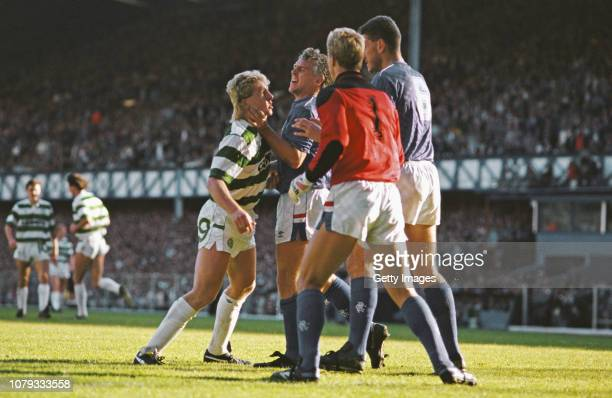 Celtic striker Frank McAvennie is held by the throat by Rangers defender Graham Roberts as goalkeeper Chris Woods and Terry Butcher look on, Butcher,...