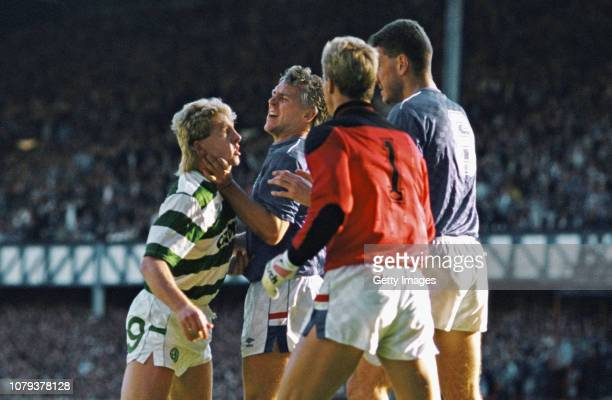 Celtic striker Frank McAvennie is held by the throat by Rangers defender Graham Roberts as goalkeeper Chris Woods and Terry Butcher look on Butcher...