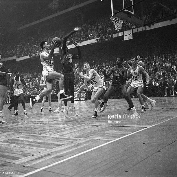 Celtics' Bob Cousy drives in hard past the guard of Nats' Bob Hopkins to make the twohand lay up shot as Celts' Tom Heinsohn Nats' Earl Lloyd Celts'...