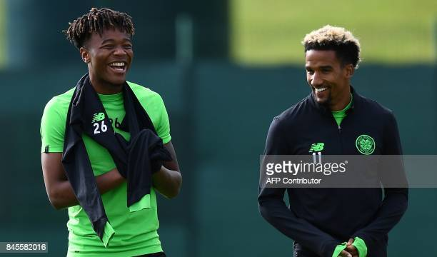 Celtic's English midfielder Scott Sinclair jokes with Celtic's English midfielder Kundai Benyu at the start of a training session at their Lennoxtown...