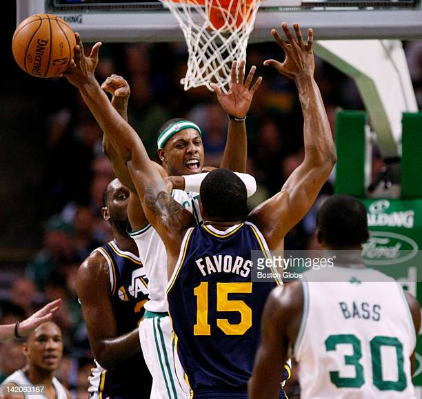 Celtics forward Paul Pierce drives and kicks out a pass deflected by Utah forward Derrick Favors but ending up in the hands Celtics forward Brandon...