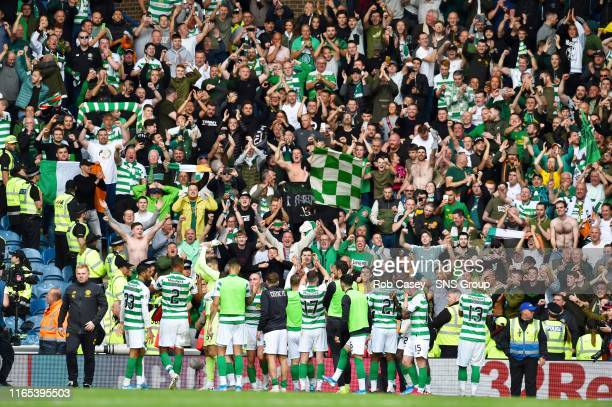 Celtic's players celebrate with their fans during the Ladbrokes Premier match between Rangers and Celtic at Ibrox Stadium, on September 1 in Glasgow,...
