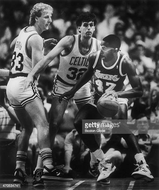 Celtics players Larry Bird and Kevin McHale stop a Lakers player during an NBA Finals game at Boston Garden on June 9 1987