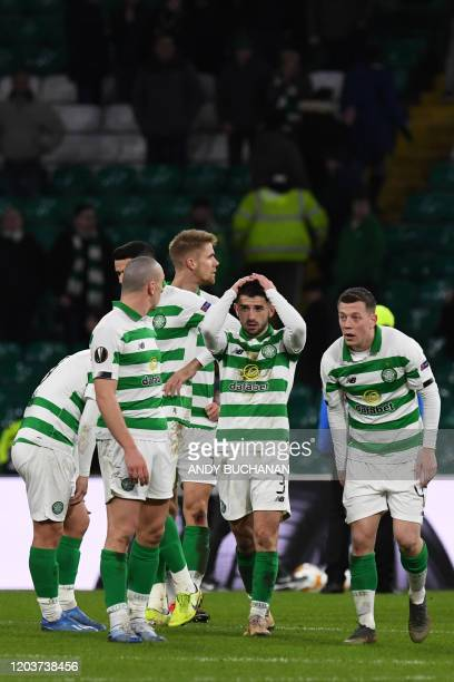 Celtic's Scottish defender Greg Taylor and teammates react to their defeat on the pitch after the UEFA Europa League round of 32 second leg football...