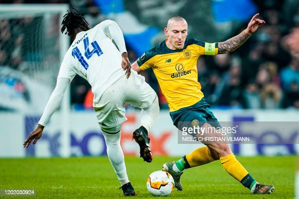 Celtic's Scottish midfielder Scott Brown and FC Copenhagen's Senegalese forward Dame N'Doye vie for the ball during the Europa League last 32 first...