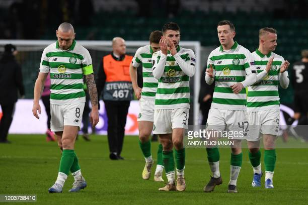 Celtic's Scottish midfielder Scott Brown and teammates react to their defeat on the pitch after the UEFA Europa League round of 32 second leg...