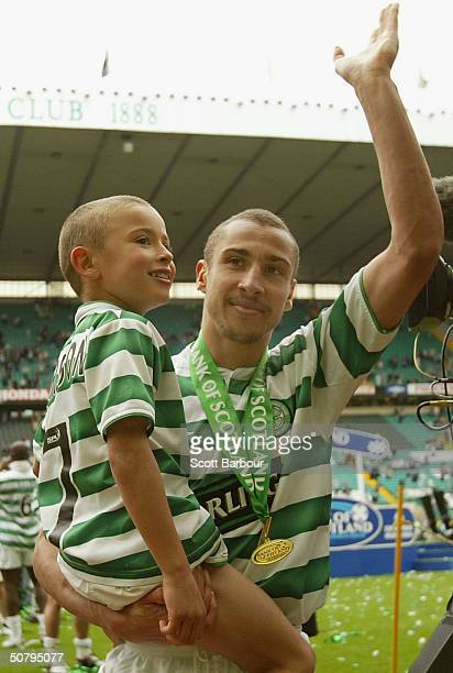 Celtic's Swedish striker Henrik Larsson does a lap of honour with his son after being presented with the Scottish Premier League Trophy after the...