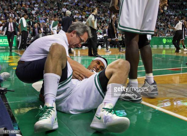 Celtics trainer Ed Lacerte tends to injured guard Courtney Lee as Dr Brian McKeon the team doctor rushes in to help as well The Boston Celtics hosted...