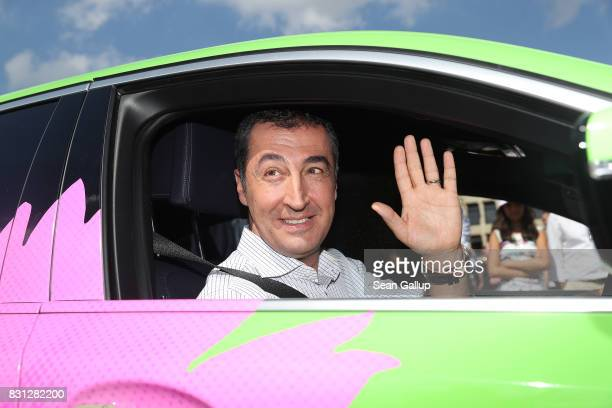 Cem Oezdemir colead candidate of the German Greens Party waves from a BMW hybrid car as he sets off on his election campaign tour following the tour...