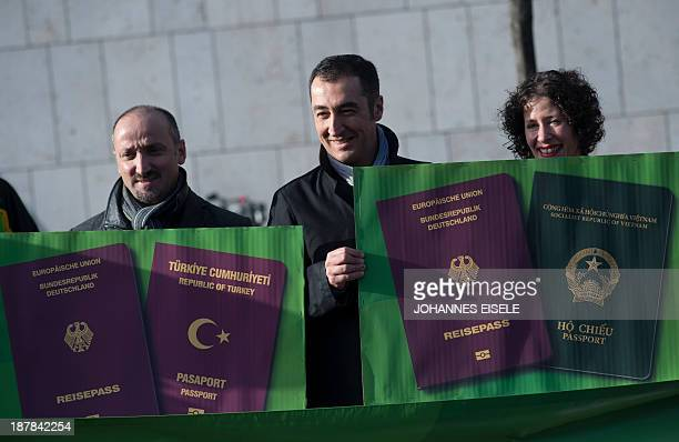 Cem Oezdemir coleader of Germany's Greens party and other demonstrators holds up poster showing German Turkish and Vietnamese passports as they...
