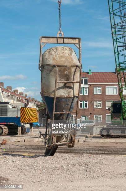 cement dump hangs from a crane