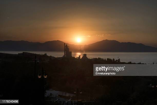cement factory silhouette at sunset at edremit,van lake. - emreturanphoto stock pictures, royalty-free photos & images