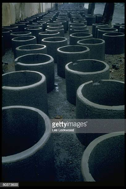 Cement liners for bomb shelters sitting on street in front of manufacturing plant