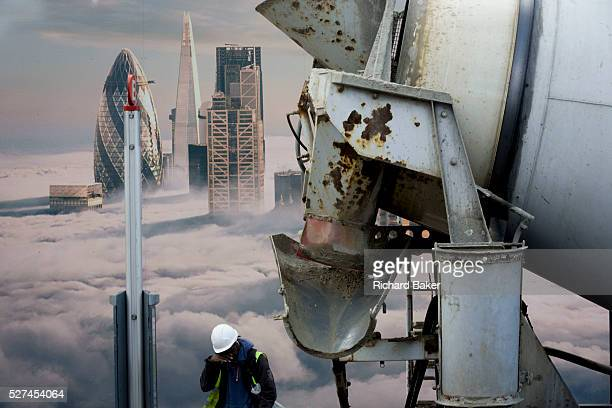 Cement mixer lorry and construction workman beneath a property developer's billboard on Shoreditch High Street showing a large aerial image of London...