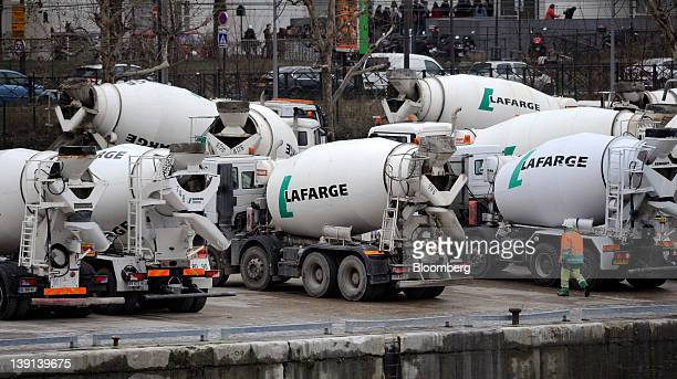 Cement mixer trucks sit parked on the quay side at a Lafarge SA depot in Paris France on Thursday Feb 16 2012 Lafarge SA jumped as much as 45 percent...