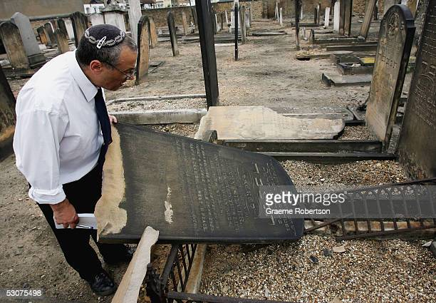 A cemetary caretaker inspects the damage to Jewish gravestones in the East Ham Jewish cemetery June 16 in London England AntiSemitic vandals damaged...