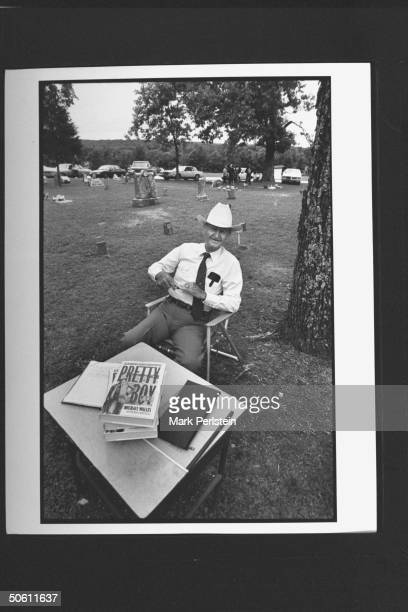 Cemetery caretaker Corbuy Let sitting on chair by table while selling Michael Wallis' bk PRETTY BOY in the cemetery in which murderous bank robber...