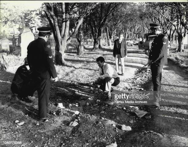 Cemetery' Detectives and uniformed police crouch to inspect the scene amongst headstones where a 55yearold man was found shockingly bludgeoned in...