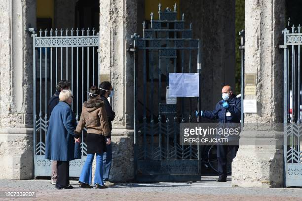 Cemetery employee wearing a face mask closes the gates of the Monumental cemetery of Bergamo, Lombardy, as relatives of a deceased person wait...