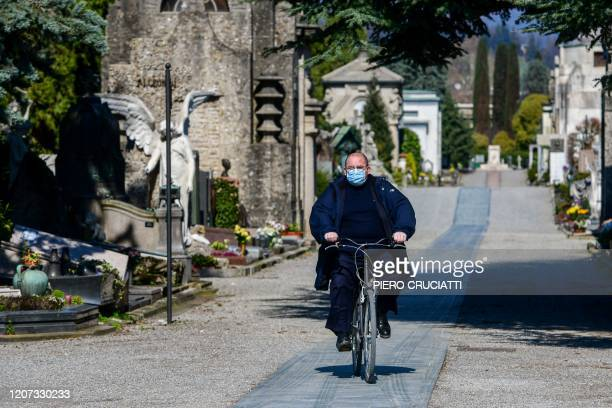 A cemetery employee wearing a face mask rides a bicycle across the Monumental cemetery of Bergamo Lombardy on March 16 as burials of people who died...