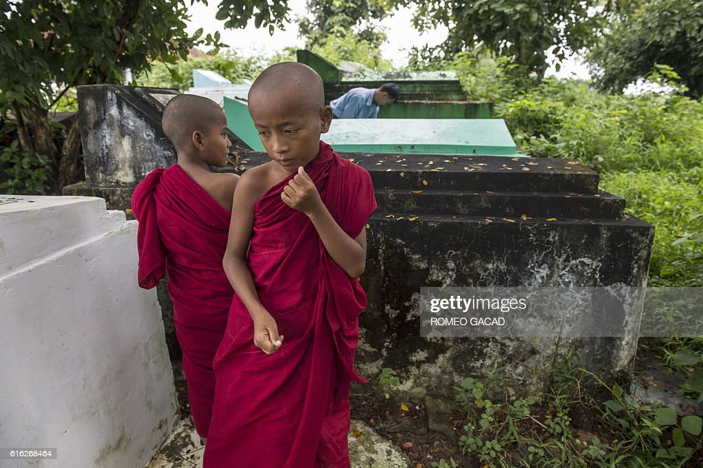 Cemetery personnel bury the body of three-year-old Nay La Linn, a victim of an exorcism ritual, at a public cemetery in Twante town, south of Yangon on October 22, 2016, as young novice monks looks on. Three infant children have been beaten to death in a Myanmar village outside Yangon by a man purporting to be a spiritual healer, who told their families they were possessed by evil spirits. / AFP / ROMEO