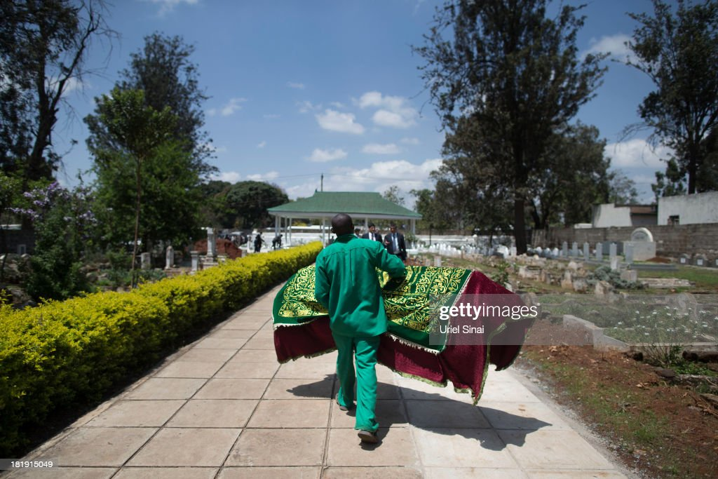 A cemetery worker carries a coffin cover during the funeral ceremony of Ruhila Adatia Sood, A Radio Africa television and radio presenter, on September 26, 2013 in Nairobi, Kenya. The country is observing three days of national mourning as security forces begin the task of clearing and securing the Westgate shopping mall following a four-day siege by militants.