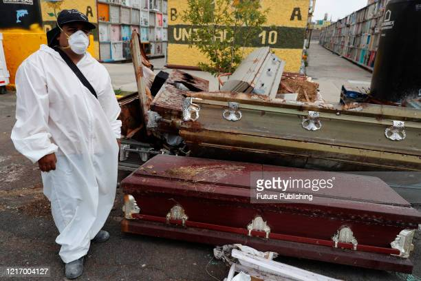 A cemetery worker wears protective gear while walks next to coffins stacked at Nezahualcoyotl cemetery amid the new Coronavirus pandemic on June 2...