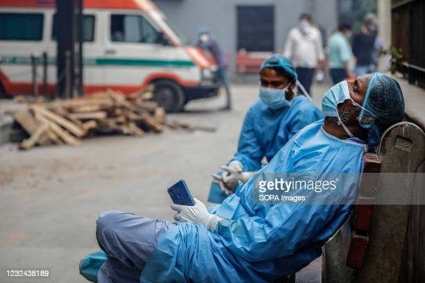 Cemetery workers helping people to cremate the bodies of their relatives who died of the Covid-19 coronavirus disease take a break at a crematorium,...