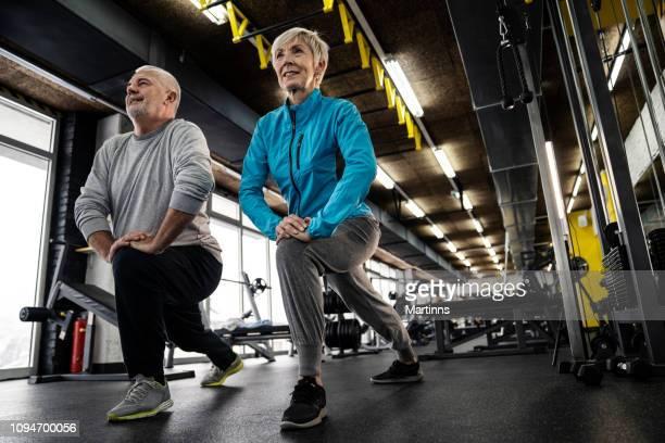 cenior casal fazendo exercícios na academia - treinamento esportivo - fotografias e filmes do acervo